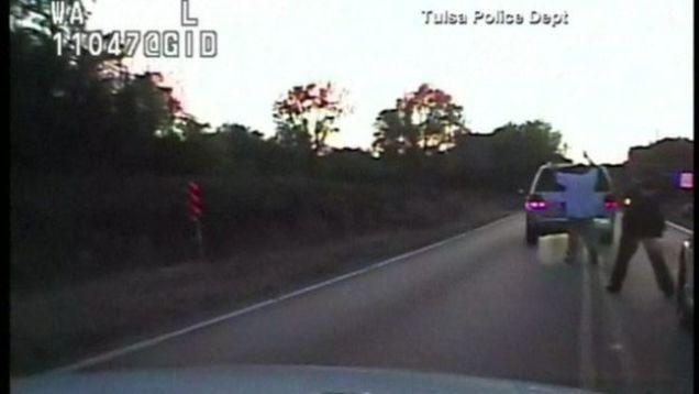 Mientras está rodeado por cuatro policías, Crutcher aparentemente recibe un disparo de arma de electrochoque y luego otro de fuego.Tulsa Police Department/Reuters