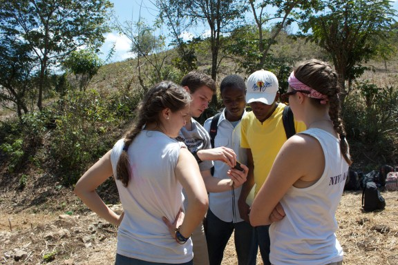 Ford, Linnea and Sega walk their group members through using a hand held GPS.