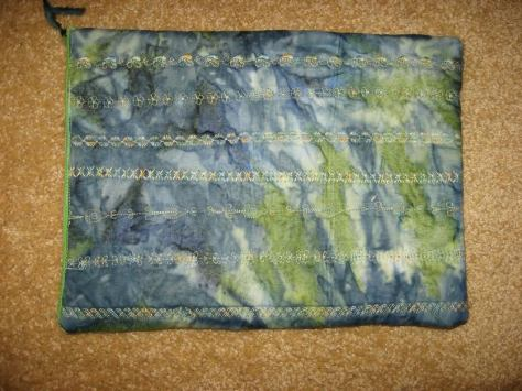 """by Eileen Diercks - """"From the Danish/American challenge fabric I made a zippered pouch for my Kindle and its charging cord.   I used some of the """"fancy"""" stitches on my machine, using a variegated green, blue and yellow thread which I had on hand, for the quilting.  For the lining I used a lime green batik fabric which I had in my stash, and the green zipper was also from my sewing supplies.  So it did not cost me anything extra for this handy pouch. Thanks for the challenge."""""""