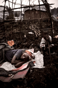 A mother rests before finishing her shelter at the Mugunga I site for internally displaced people in Goma, North Kivu Province, Democratic Republic of the Congo, on Feb. 22, 2008. This picture resembles many others taken this month. The Rwandan and Ugandan M23 militia surrounds Goma, even though it has formally withdrawn in response to international pressure. Sources in Goma say the people are terrified.  The UNHCR says that 900,000 more people have been made homeless by M23's war since April, and over 750 children have been reported missing. – Photo: © A. McConnell, WpN