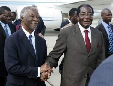 Zimbabwe President Mugabe walks with South Africa President Mbeki on his arrival in the capital Harare