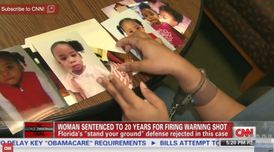 In handcuffs, Marissa looks at pictures of her children. – Video frame: CNN