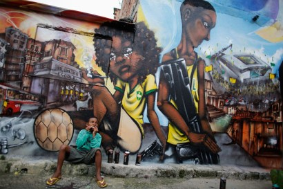"Ryan, 9, sits in front of graffiti painted by members of Unidentified Graffiti Artists (OPNI) protesting the 2014 World Cup in the Vila Flavia ""slum"" of Sao Paulo on May 28, 2014. – Photo: Nacho Doce, Reuters"