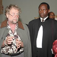 """International criminal defense attorney Peter Erlinder – in handcuffs for """"genocide denial"""" – appears in a Kigali, Rwanda, courtroom with Kenyan lawyer Kennedy Ogetto in May 2010."""