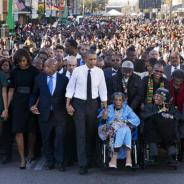 The Obamas lead a march in Selma on Saturday, March 7, marking the 50th anniversary of Bloody Sunday, the president holding the hands of two veterans of the struggle for voting rights, Congressman John Lewis and Amelia Boynton Robinson, 103. Both were severely beaten by state troopers on Bloody Sunday, March 7, 1965. The other wheelchair user is educator Adelaide Sanford, a founder of Elder's House, a history repository and learning center in Selma. – Photo: Jacquelyn Martin, AP