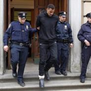 NYPD officers lead Thabo Sefolosha, grimacing in pain, out of the police station after booking him.