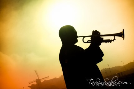 Larry Douglas' trumpet welcomed the sunrise at Ocean Beach – the iconic old Dutch windmill in the background. – Photo: TaSin Sabir