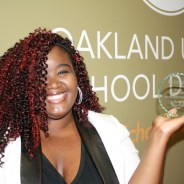 Ty-Licia Hooker, executive director of Boost! West Oakland, proudly displays the Oakland Unified School District's Partner Organization of the Year Award they won.