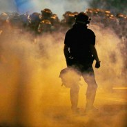 "The caption for this photo written by The Associated Press describes police-initiated violence: ""Police fire teargas as protestors converge on downtown following Tuesday's police shooting of Keith Lamont Scott in Charlotte, N.C., Wednesday, Sept. 21, 2016. Protesters have rushed police in riot gear at a downtown Charlotte hotel and officers have fired tear gas to disperse the crowd. At least one person was injured in the confrontation, though it wasn't immediately clear how. Firefighters rushed in to pull the man to a waiting ambulance."" – Photo: Gerry Broome, AP"