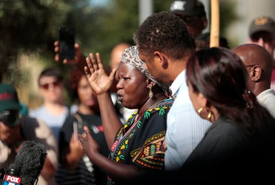 Agnes Hassan, a family friend of the Alfred Olango, speaks to protesters gathered at the El Cajon Police Department headquarters to protest the fatal shooting of the unarmed Black man Tuesday by officers in El Cajon. – Photo: Earnie Grafton, Reuters