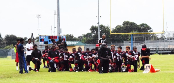 "Members of the Texas youth football team, the Beaumont Bulls, take a knee to ""protest violence against Black youth"" during the national anthem before their Sept. 10 game. – Photo: April Parkerson"