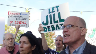 Outside the Clinton-Trump debate at Hofstra University, Cheri Honkala, housing activist and 2012 Green Party vice presidential candidate, and David Cobb, lawyer and 2004 Green Party presidential candidate, protest the exclusion of Jill Stein by the Commission on Presidential Debates, which is composed of the Democratic and Republican parties.