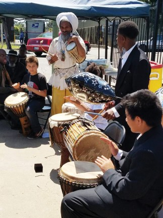 Graduates of Deecolonize Academy, the school at Homefulness, took a break from their commencement last May 26 for an emergency press conference on displacement to protect, among many others, their teacher, the beloved musician Val Serrant, who faced eviction. – Photo: Poor News Network
