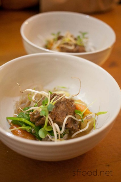 Braised short ribs in a conconut broth with smokes potatoes and thumbelina carrots with mung bean sprouts