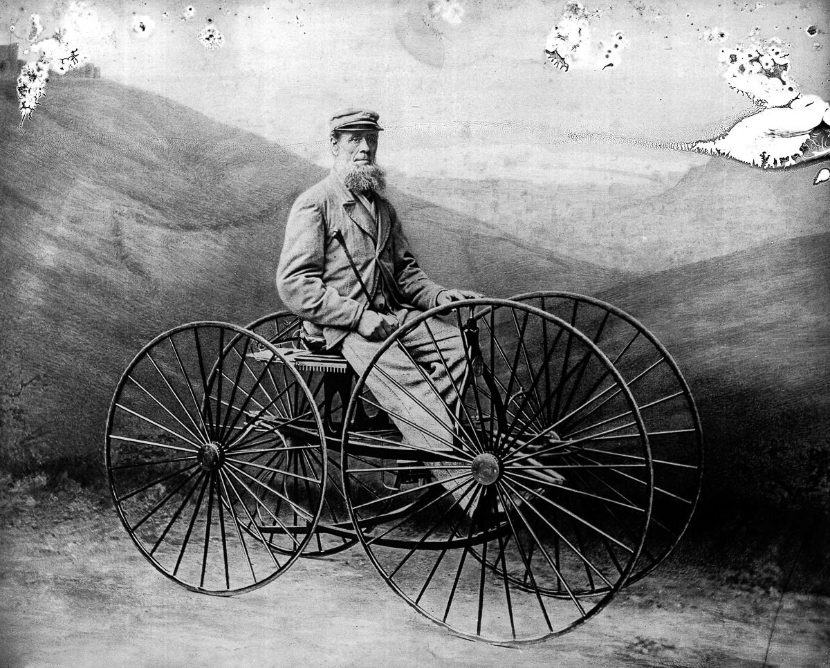Man sitting on four-wheeled velocipede, 19th century.