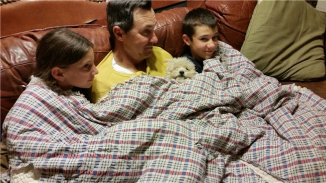 Nathan, the kids and Daisy cuddle on the couch