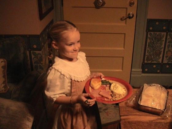 Ellie in her pilgrim clothes at close of Thanksgiving day. She's having left overs from the big meal.