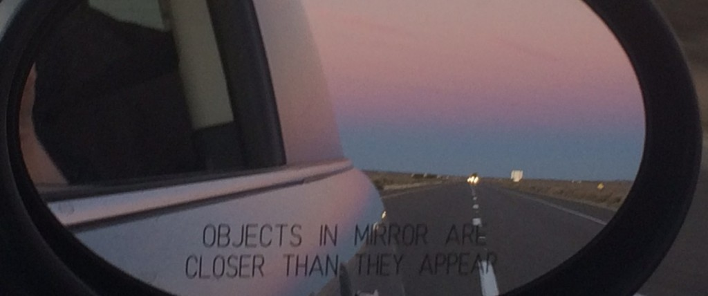 sunset in the rear view mirror of a Mini Cooper