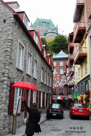 一名导游举着一把红雨伞带领旅客 (魁北克古城)