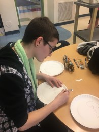 Sophomore CJ Medley cuts out a chameleon stencil for the children to use in their craft.