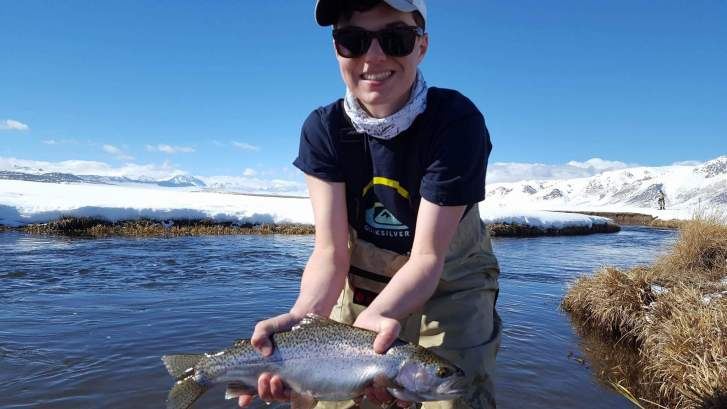 Young man holds big Trout while fishing on the Upper Owens River with STM Fly Fishing
