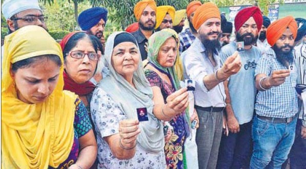 Parents of the youths arrested by the police with photographs of their wards before meeting Akal Takht jathedar Giani Gurbachan Singh in Amritsar