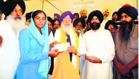 SGPC chief Avtar Singh Makkar hands over a cheque to a family member of a Sikh farmer displaced from Haryana