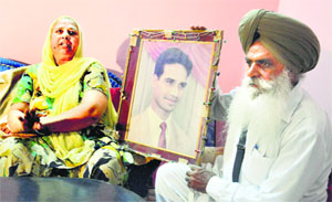 Charanjit Kaur and Amrik Singh with picture of their son Avtar Singh, who was allegedly killed by Gurmeet Singh