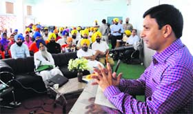 Deputy Commissioner Ravi Bhagat addresses volunteers of Akal Purkh Ki Fauj at Bhai Gurdas Hall in Amritsar