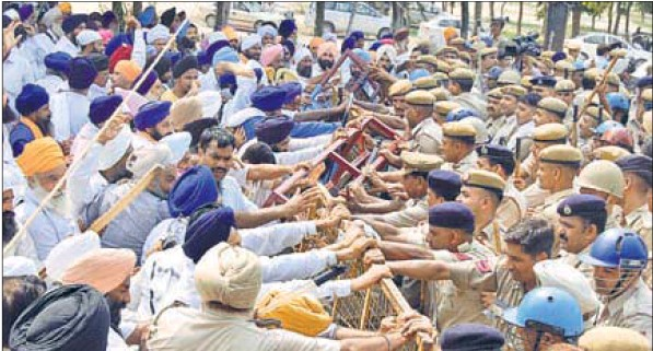 HSGMC supporters up against cops at a barricade near Gurdwara Chhevin Patshahi in Kurukshetra on Sunday. Storming of gurdwaras last option, says HSGMC chief as supporters arm themselves.