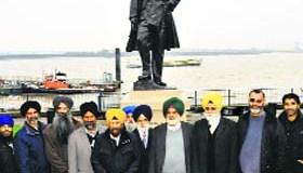 Members of Guru Nanak Darbar Gurdwara, Gravesend, pose in front of the Sikh soldier's statue in London.