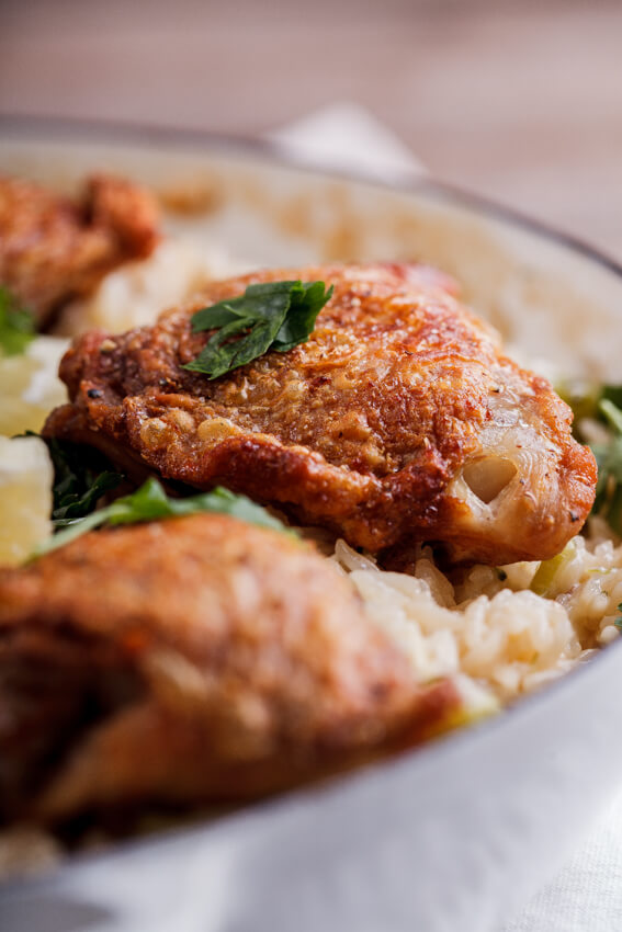 Crispy chicken thighs on cheesy broccoli rice