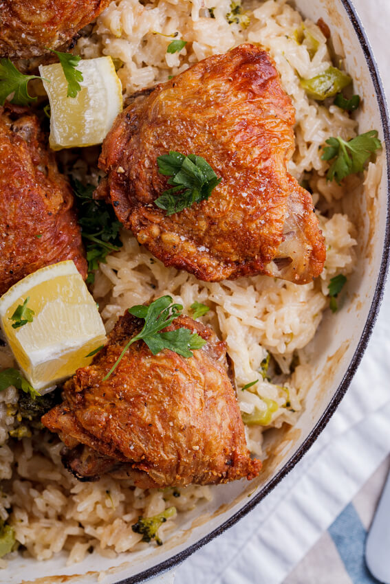 Crispy chicken thighs on cheesy broccoli rice