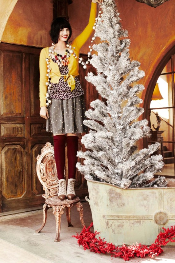 Woman standing on a chair to put her ornaments high on the tree