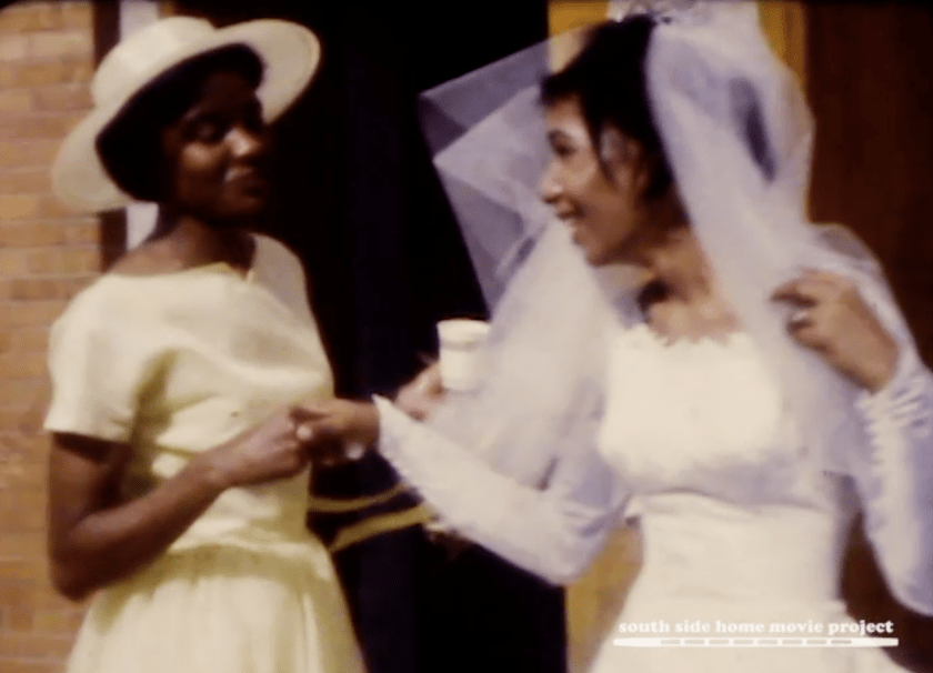Film still of a dark-skinned Black woman in a light yellow dress smiling and holding the hand of a lighter-skinned Black woman in a white wedding dress with a veil. Courtesy of the South Side Home Movie Project.