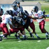The East defense attempts to strip the ball from a Lawrence running back. Photo by Julia Poe
