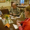 Juniors Mary Locascio and Kennedy Webb play cards with a Brighton Gardens resident. Photo by Paloma Dickey