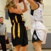 Jean Phillips jumps to block opposing player from making a basket. By Katie Lamar