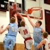 Junior Lucas Jones and sophomore Joey Wentz block a shot by senior Connor Henrichs. Photo by Katie Lamar