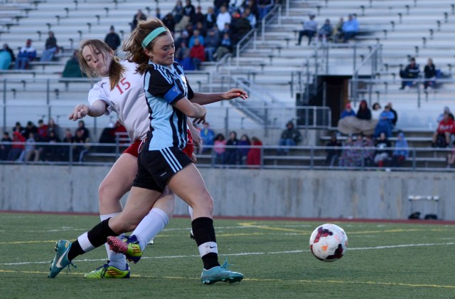 Junior Emma Braasch powers through opponent to reach the ball. By Katie Lamar