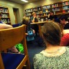 Poets sit around librarian Kathleen Knop as she plays sophomore Lily Osborn's poem.