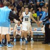 Junior Jay Guastello high fives his teammates as he prepares for tip-off. Photo by Joseph Cline.