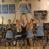 Varsity basketball players hold senior Jack Flint up in a stunt during their routine. Photo by Callie McPhail