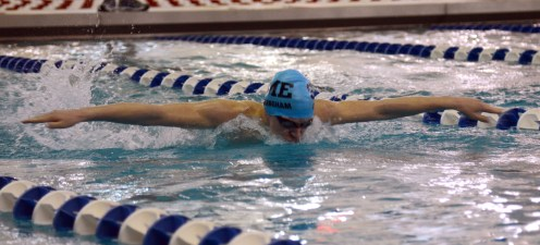 Freshman Tyler Cunningham swings his arms forward during the 100 yard Butterfly. Photo by Annie Lomshek.