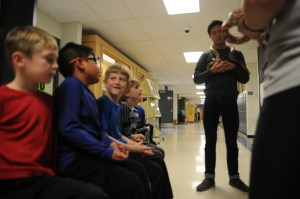 Students sit in hallway and learn more about snakes