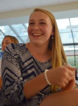 Sophomore Fallon Herrick laughs along the slideshow that she put together for the banquet. Photo by Annie Lomshek.