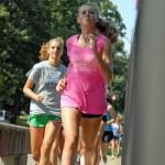 Junior Emma Cannova and Sophomore Peyton Hassenflu run across a bridge.  Photo by Tess Iler