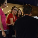 Seniors Elsa Bernauer, Leah O'Connor and Catherine Beasley practice their group number with Choir Director, Mr. Foley, after the dress rehearsal. Photo by Morgan Browning
