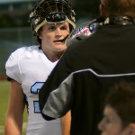 Senior Calvin Jones listens to head football coach Delaney as he discuses the previous play. Photo by Kaitlyn Stratman