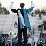 The conductor silences the band after finishing their performance at the start of the game. Photo by Ellie Thoma
